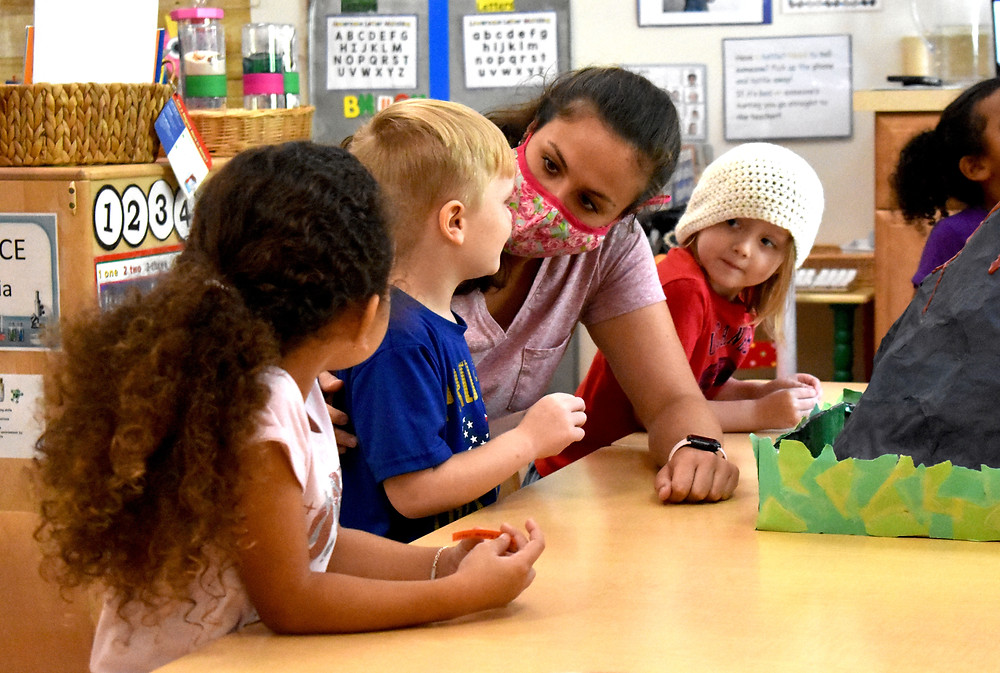 A young woman sits next to three preschool students at a table. The woman is speaking to one of the students.