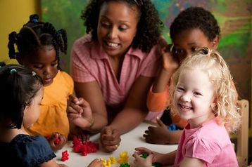 A teacher sits at a table with a group of preschool students. They are playing with small toys.