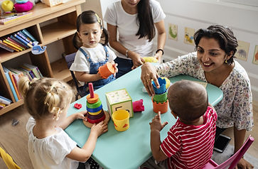 A teacher sits with students at a table. The students are playing with stacking toys.