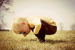 A young child examines grass with a magnifying glass.