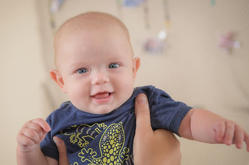 A baby is held up, smiling at the camera
