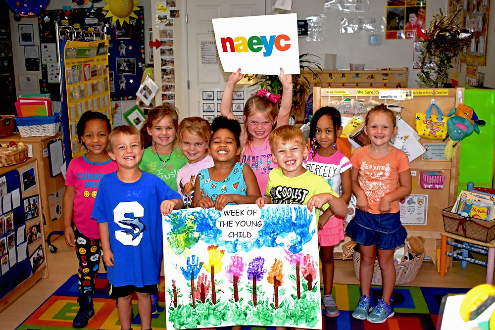 "A group of children stand together in a classroom, holding signs that say ""NAEYC"" and ""Week of the Young Child"""