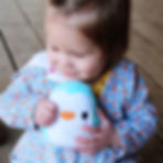 Baby girl with blue penguin plushie.jpg