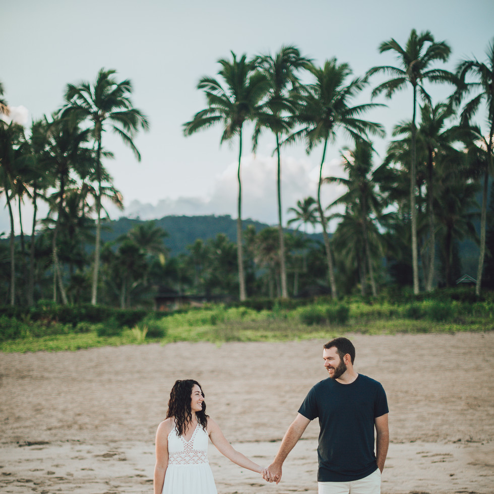 couple holding hands on beach in kauai