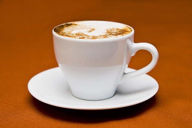 White coffee cup and saucer on a wooden table.