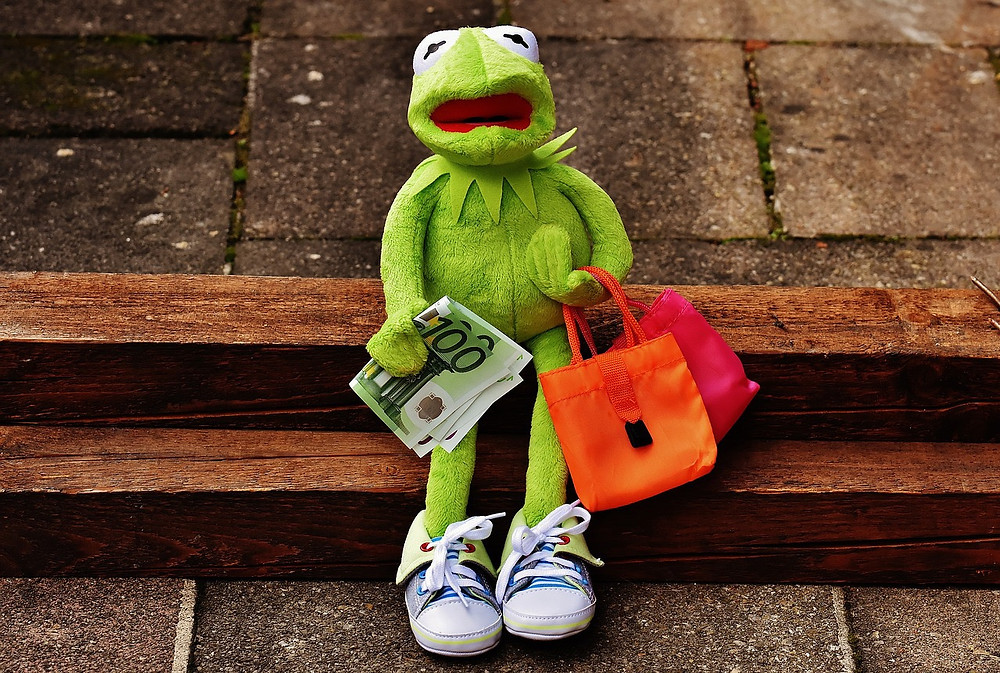 Toy frog with his mouth open, holding cash and bags.