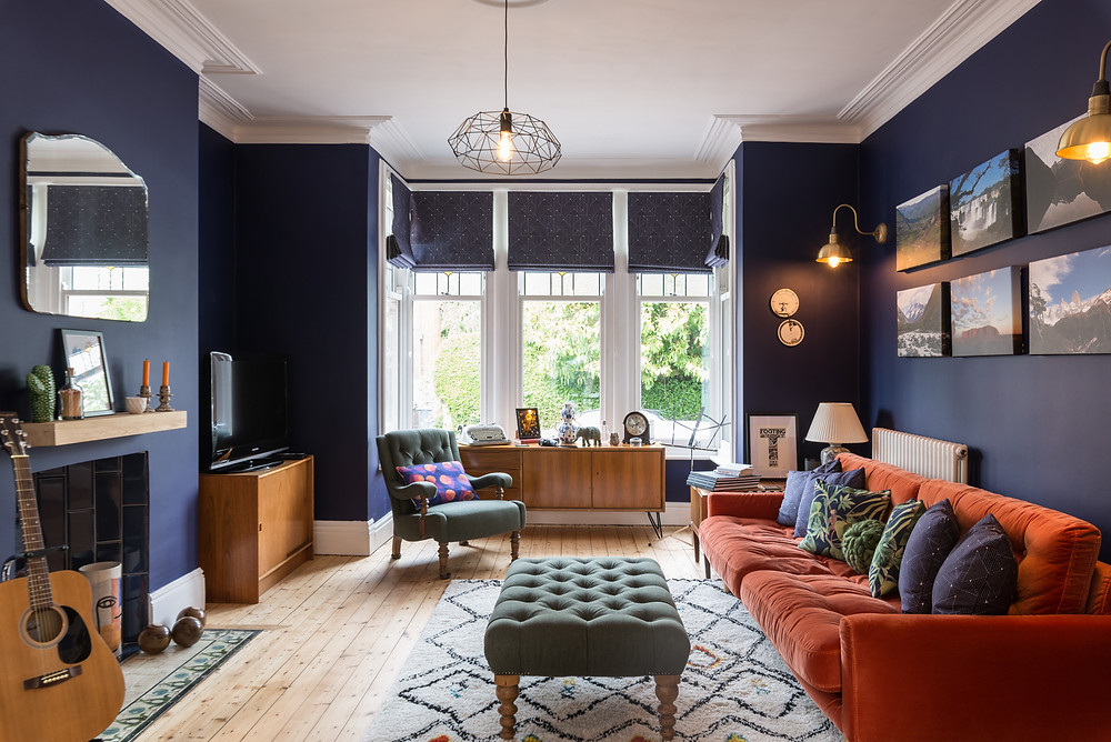 Dark blue living room with period features and orange sofa