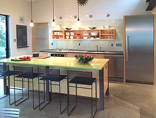 green kitchen, modern kitchen, drop pendant lighting, stainless steel appliances, stainless steel refrigerator, concrete flooring, richlite, caesarstone countertops