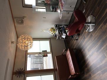 セット面1台のアットホームなサロン、オレンジ色照明、レザーソファ、木目調の床