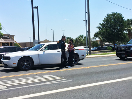 Police Officer helps woman carrying toddler girl