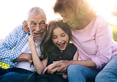 senior-couple-with-granddaughter-outside