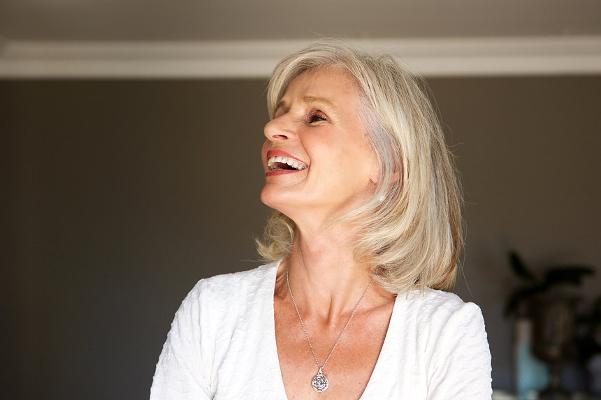 laughing-older-woman-standing-inside-hom