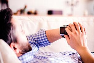 man-lying-on-sofa-at-home-using-smart-wa