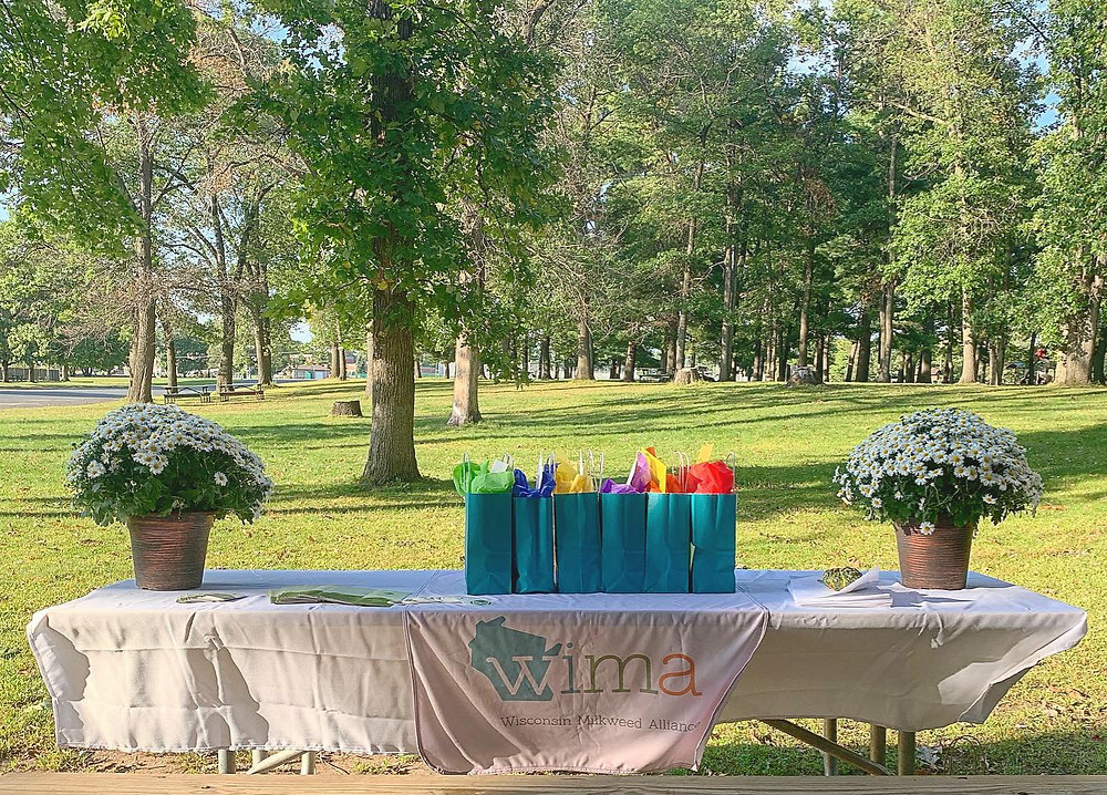 A table display from the annual meeting with flowers, gift bags, and a table cloth with the WIMA logo. In the background are trees and grass.