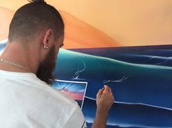 Street artist painting ocean mural