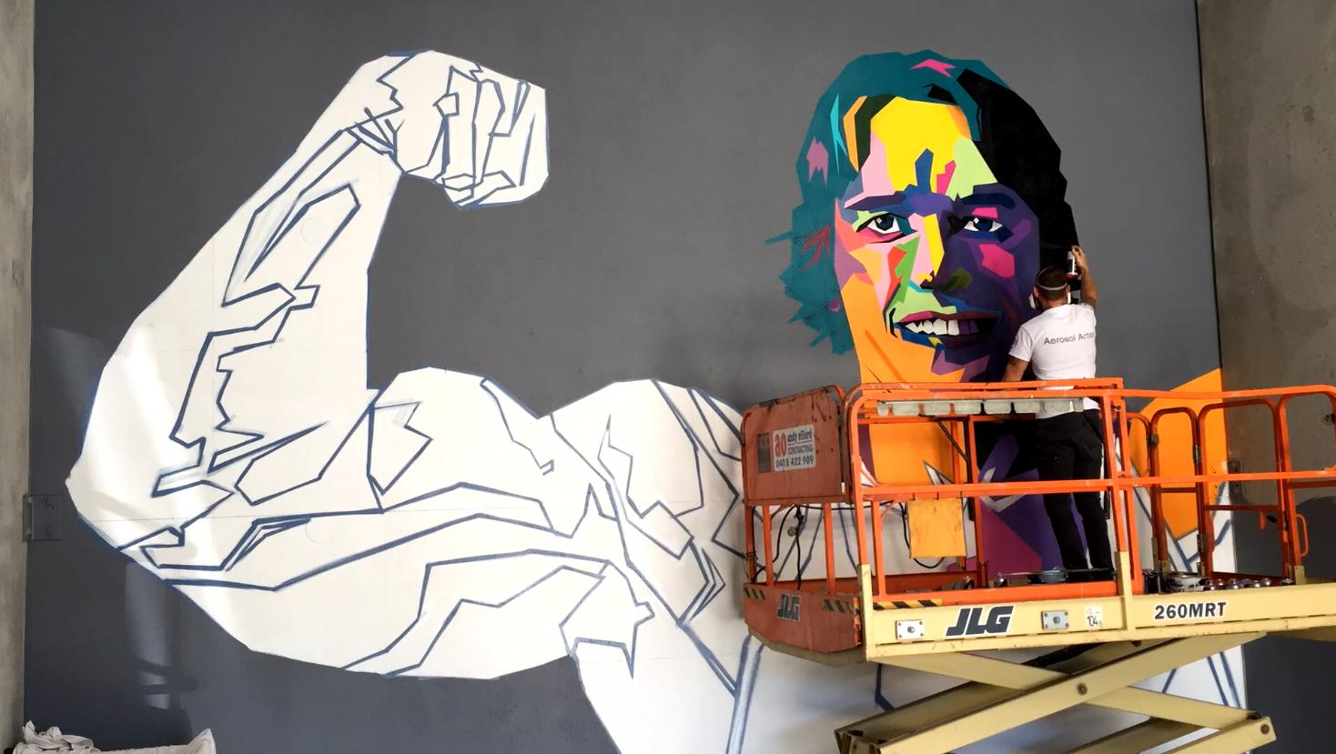street artist painting mural of Arnold schwarzenegger
