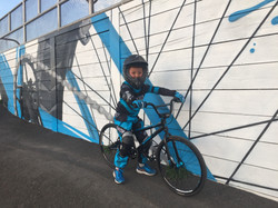 cute kid on BMX in front of mural art