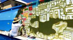 Street artist in action painting mural Urban Art