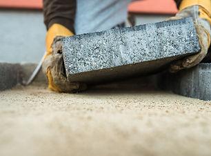 builder-laying-a-paving-brick-placing-it-on-the-sa-C9ATHJ2.jpg