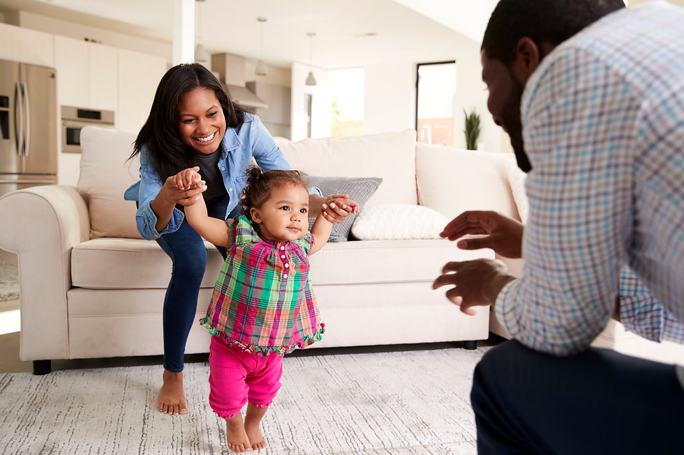 family-at-home-encouraging-baby-daughter-to-take-f-6WS9BA5.jpg