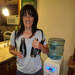 trusii, Woman holding three trusii water bottles and smiling
