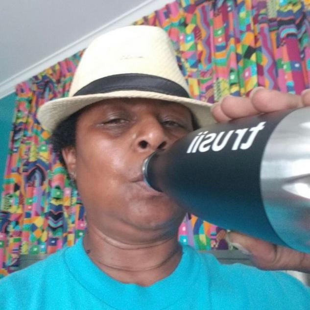 trusii, man wearing hat drinking trusii water