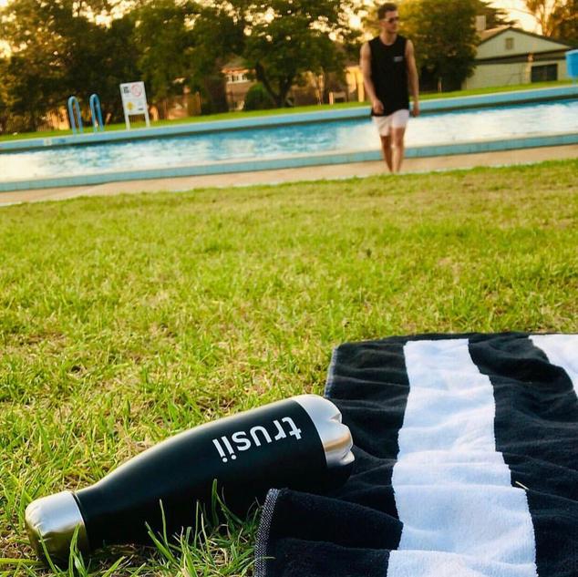 trusii, trusii bottle next to beach towel