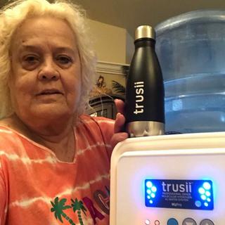 trusii, Older woman posing with trusii ProElite and hydrogen water bottle