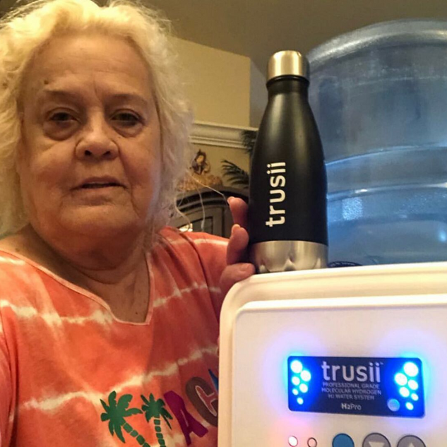 trusii, Older woman posing with trusii ProElite and hydrogen water bottle