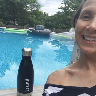 trusii, Woman by pool with trusii bottle