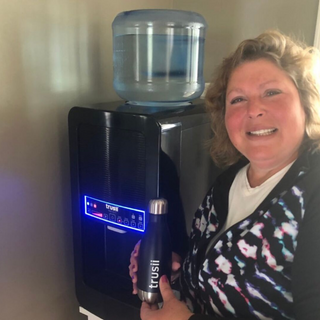 trusii, woman smiling with trusii bottle and EliteX system