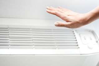 Hand hovering over an air conditioning unit