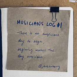 """Blue writing on brown paper, clipped to a notebook: """"Musician's Log #1. There is no auspicious day to begin, beginning makes the day auspicious."""""""