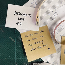 """Writing on scraps of paper, sitting on manuscript paper, a cutting board and a sewing tape measure: """"Not the calm after the storm, but the birdsong after the rain."""""""