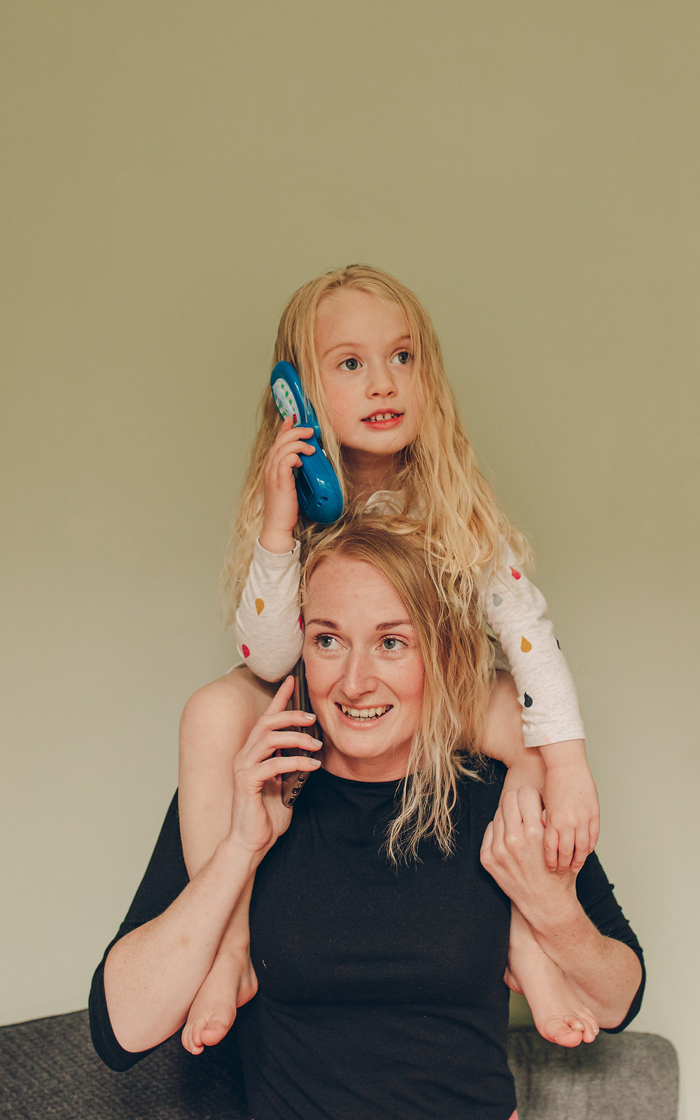 A woman is on the phone with her toddler daughter on her shoulders holding a toy phone and mimicking the pose