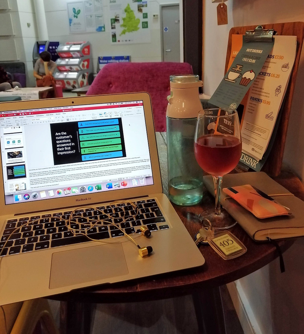 a laptop computer, glass of wine and hotel key
