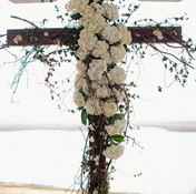 Beautiful wedding cross with flowers at the alter