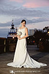 Bride standing on river dock with a beautiful sunset in the background