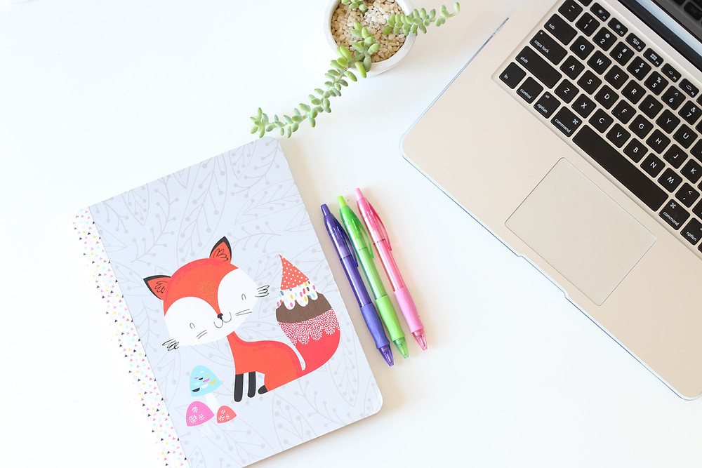 Graphic- notebook with fox on cover next to color pencils
