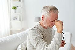 healthcare, pain, stress, age and people concept - senior man suffering from headache at home.jpg