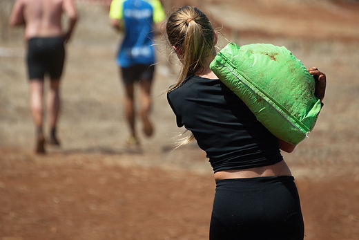 Mud race runners,young woman running wit