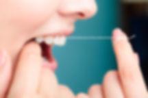 woman flossing her teeth - The Teeth Peo