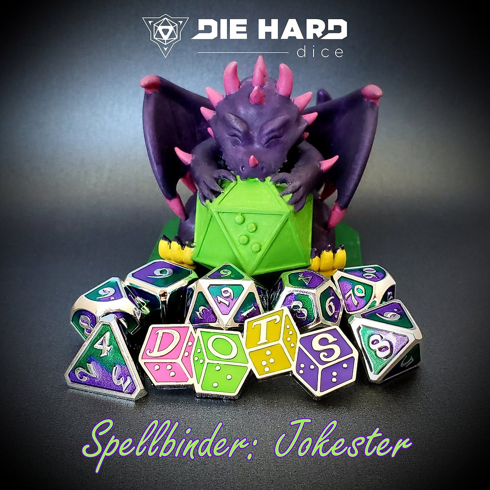 DOTS Dragon with a pile of metal dice and DOTS logo pin. Dice are a silver metal with two tone glittering purple and green enamel on each face. Text: Die Hard Dice logo and Spellbinder: Jokester.