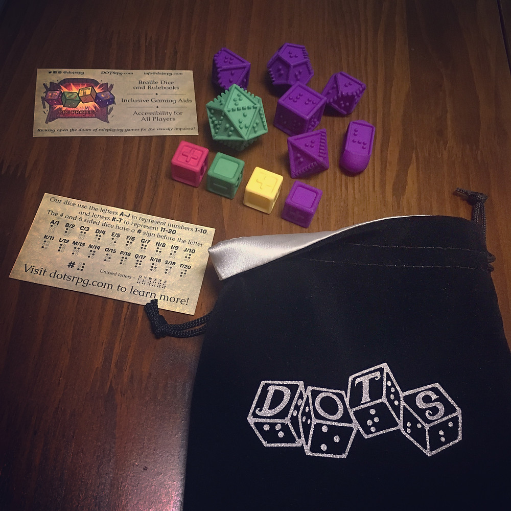 Dice bag, braille dice (purple set with green d20) and tactile fate dice (pink, green, yellow, and purple to match the dots logo). Business cards with braille guide included.