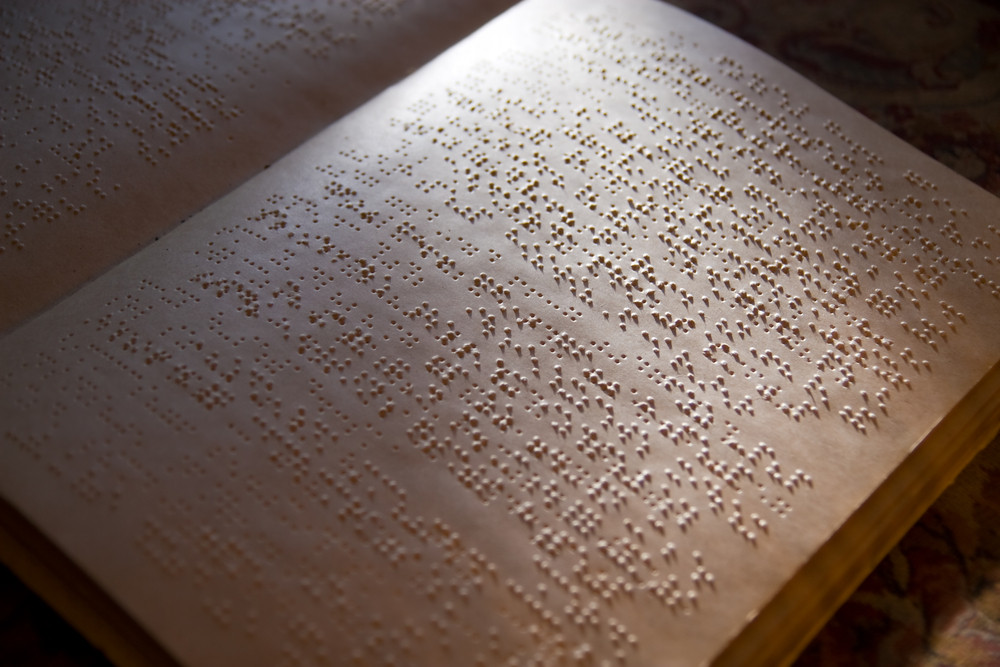 Book open showing two pages with braille lit dramatically from one corner, casting long shadows over the double sided interpoint braille.