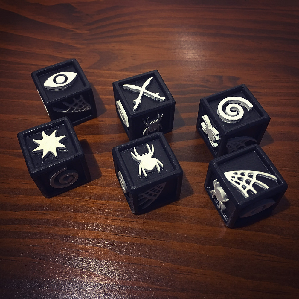 Set of 6 d6 on a wooden table. Dice are black with tactile white symbols: eye, crossed scimitars, spiral, sun, spider, web