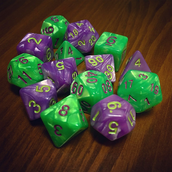mixed pile of swirled purple plastic with green number and swirled green plastic with purple number dice