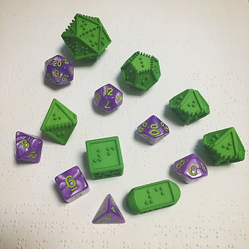 Set of 7 3d printed green rpg dice with braille letters in place of written numbers. Dice are next to 16mm written numbered dice, the braille dice about twice the size