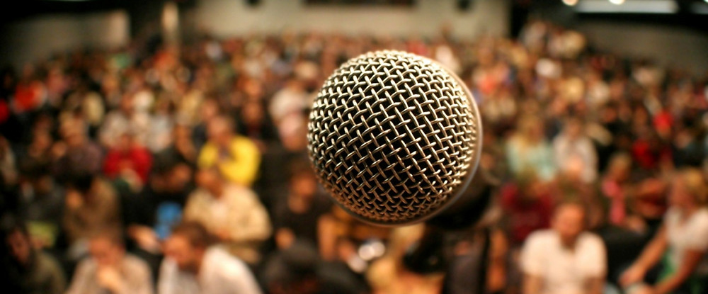 Close up of speaker's microphone showing audience in the blurry background.