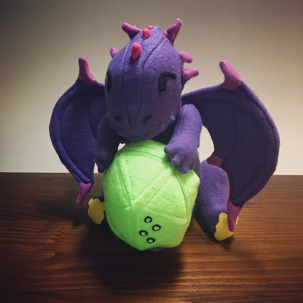 Plush DOTS dragon: Western style dragon with purple body and wings. Pink accents with horns, wing tips, and tail accents. Yellow belly. Dragon is holding a bright green d20 with the braille symbol for T (20 on our dice) on one face.
